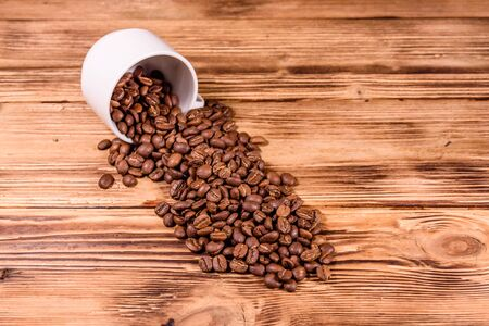 White cup and scattered coffee beans on rustic wooden table