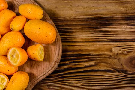 Cutting board with kumquat fruits on a wooden table. Top view