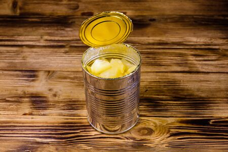 Aluminium tin can with chopped canned pineapple on rustic wooden table