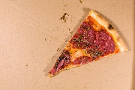 Last piece of pizza with salami sausage and parmesan cheese in cardboard box Stok Fotoğraf