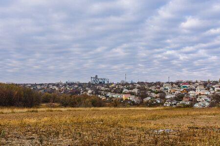 Plowed field at autumn. City Uman on background. Ukraine Banco de Imagens