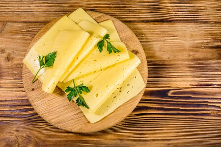 Sliced cheese and parsley on wooden cutting board. Top view