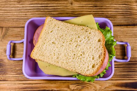 Lunch box with sandwiches on wooden table. Top view