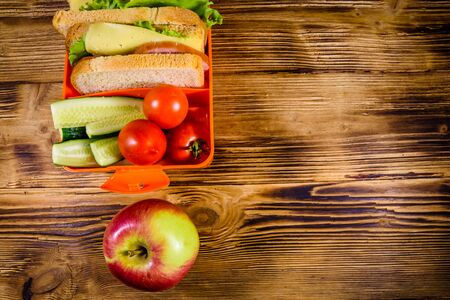 Ripe apple and lunch box with sandwiches, cucumbers and tomatoes on rustic wooden table. Top view Banco de Imagens