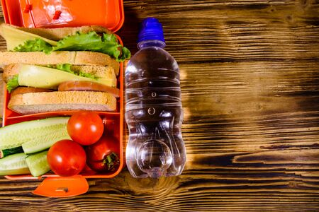 Bottle of water and lunch box with sandwiches, cucumbers and tomatoes on rustic wooden table. Top view