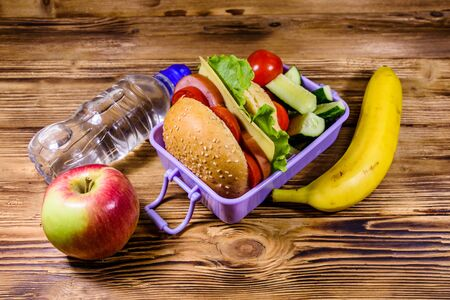 Ripe apple, banana, bottle of water and lunch box with hamburger, cucumbers and tomatoes on rustic wooden table Banco de Imagens