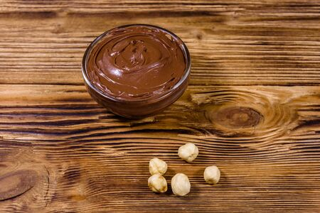 Glass bowl with chocolate spread on wooden table Banco de Imagens