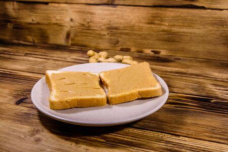 Sandwiches with peanut butter in plate on wooden table. Top view