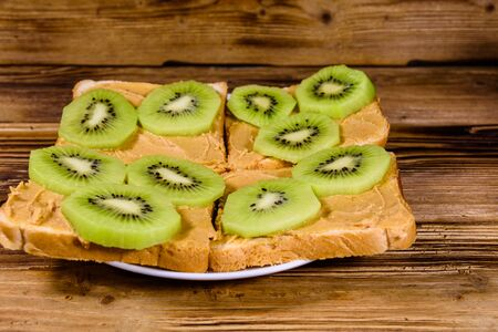 Sandwiches with peanut butter and sliced kiwi fruits in plate on wooden table Banco de Imagens
