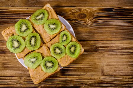 Sandwiches with peanut butter and sliced kiwi fruits in plate on wooden table. Top view Banco de Imagens