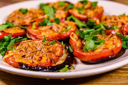 Baked eggplants with tomatoes and cheese in ceramic plate Banco de Imagens