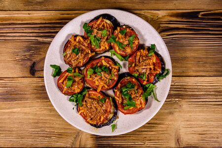 Baked eggplants with tomatoes and cheese in ceramic plate. Top view