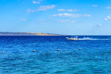 Hurghada, Egypt - December 6, 2018: Arabic man driving motorboat in Red sea not far from Hurghada city, Egypt