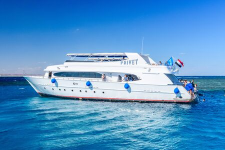 Hurghada, Egypt - December 7, 2018: People spending time on white yacht in Red sea not far from Hurghada city, Egypt