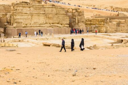 Cairo, Egypt - December 8, 2018: Arabian man with his wifes walking near the Sphinx in Giza plateau. Cairo, Egypt