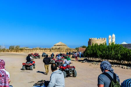 Hurghada, Egypt - December 10, 2018: Unrecognizable people driving quad bikes during safari trip in Arabian desert not far from the Hurghada city, Egypt