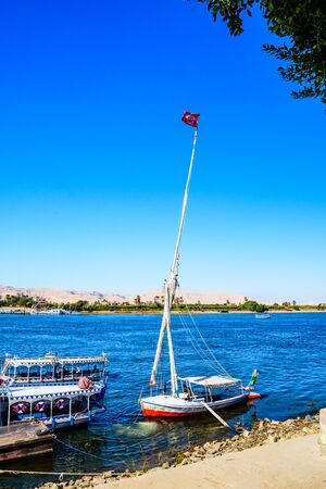 Luxor, Egypt - December 11, 2018: Felucca and tourist boats moored near the bank of Nile river in Luxor, Egypt