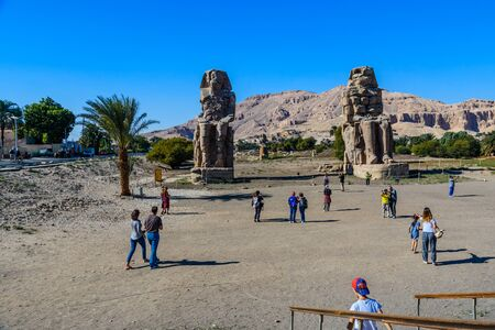 Luxor, Egypt - December 11, 2018: Tourists taking a photo of Memnon colossi (statues of Pharaoh Amenhotep III) in Luxor, Egypt