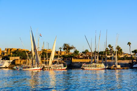Luxor, Egypt - December 11, 2018: Traditional egyptian vessels feluccas and tourist boats moored near bank of Nile river in Luxor, Egypt Editorial