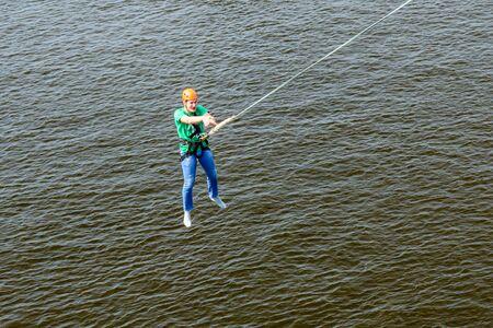 Kiev, Ukraine - July 28, 2018: Young man bungee jumper jumping from bridge