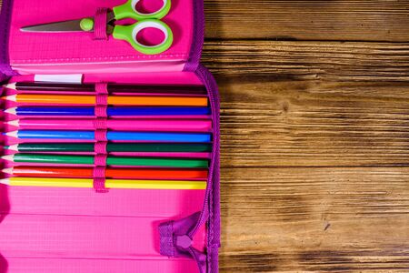 Different school stationeries (pens, pencils and scissors) in pink pencil box. Top view