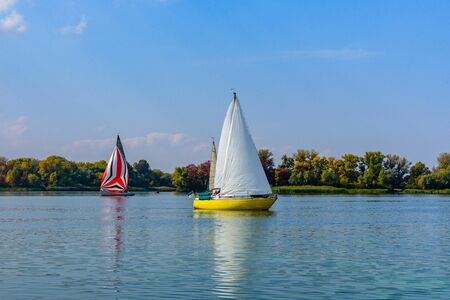 Yachts at river Dnieper on autumn in Kremenchug, Ukraine. Sailing regatta