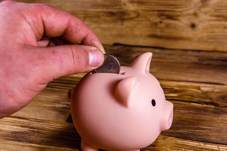 Man putting cent coin in pink piggy bank Imagens