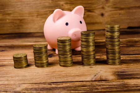 Pink piggy bank and stacks of coins on wooden background