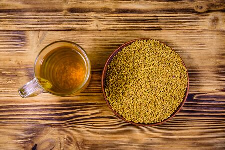 Cup of yellow tea (methi dana) and plate with fenugreek seeds on rustic wooden table. Top view