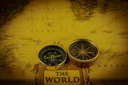 Compasses on old map of world. Journey and discovery concept
