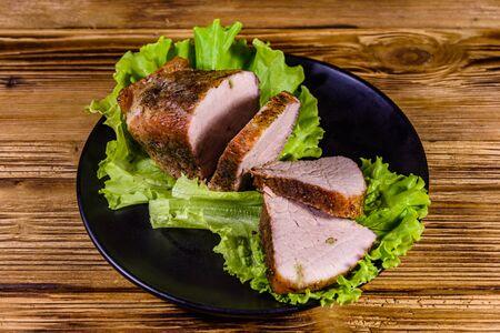 Slices of baked pork meat and lettuce leaves on black plate