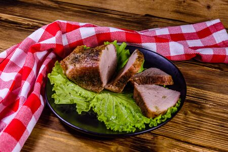 Slices of baked pork meat and lettuce leaves on black plate