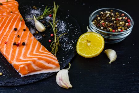 Raw fillet of salmon fish and spices on slate board