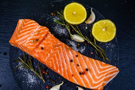 Raw fillet of salmon fish and spices on slate board. Top view