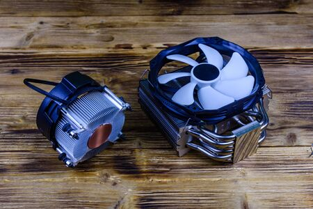 Modern cpu cooler with heat pipes. Two cpu coolers on wooden background