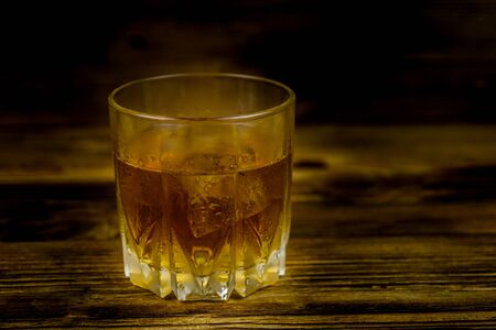 Glass of whiskey on dark wooden background