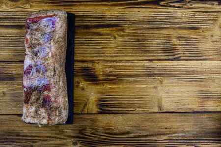 Piece of pork belly with spices on slate board. Top view