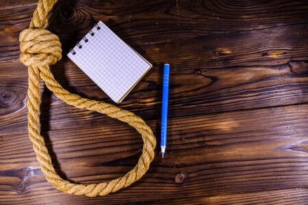 Rope with noose for suicide, blank notepad and pen on wooden background