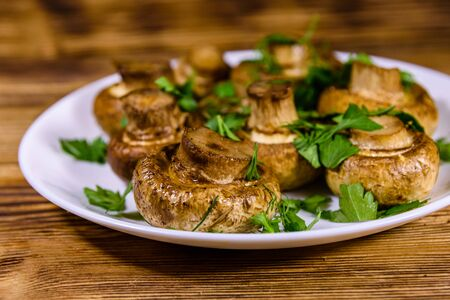 Plate with baked champignons, dill and parsley on wooden table