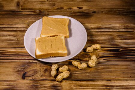 Sandwiches with peanut butter in plate on wooden table Reklamní fotografie