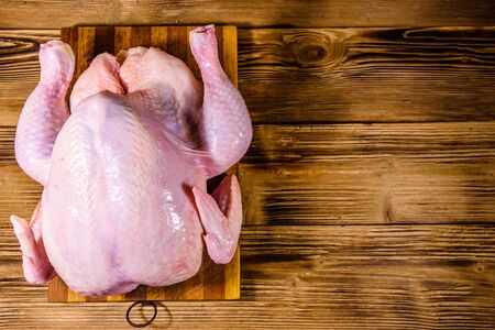 Wooden cutting board with whole uncooked chicken. Top view