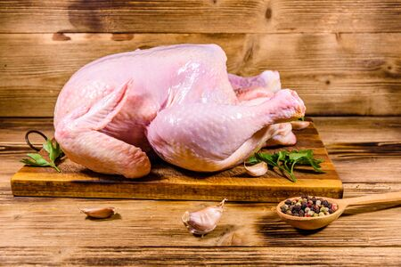 Wooden cutting board with whole uncooked chicken, garlic and spices