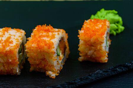 Sushi roll philadelphia with salmon, rice, cheese, cucumber, avocado and caviar on slate board. Japanese food Reklamní fotografie