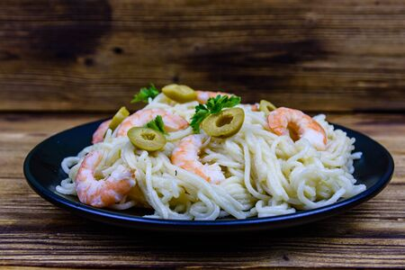 Italian pasta with shrimps and olives in black plate