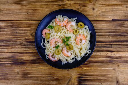 Italian pasta with shrimps and olives in black plate. Top view