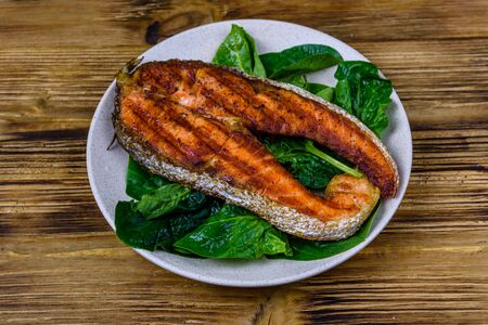 Plate with roasted salmon steak and spinach leaves on wooden table Reklamní fotografie