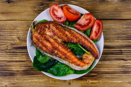Plate with roasted salmon steak, tomatoes and spinach leaves on wooden table. Top view Stock Photo