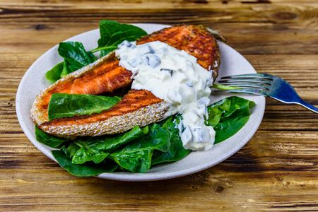 Plate with roasted salmon steak, tartar sauce and spinach leaves on wooden table Reklamní fotografie