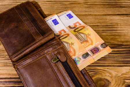 Brown leather wallet with fifty euro banknotes on wooden background