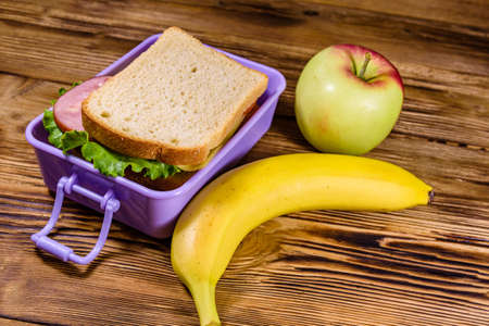 Ripe apple, banana and lunch box with sandwiches on wooden table